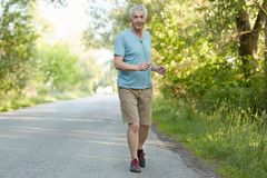 Cheerful motivated active male pensioner runs on asphalt, listens music with earphones, enjoys peaceful atmosphere and freah air i. N countryside, likes sport Stock Image