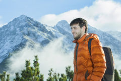 Cheerful mountain guide having rest at astonishing winter rocky landscape background Stock Photo