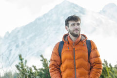 Cheerful mountaineer standing at astonishing winter high summits landscape background Royalty Free Stock Image
