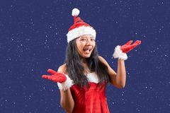 Cheerful Mrs. Claus. Looks to the camera with her hands shows stars. Stars on blue background around Mrs Claus royalty free stock photography