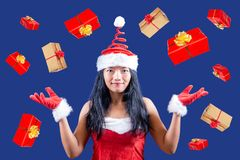 Cheerful Mrs. Claus juggle with Christmas gifts. Cheerful Mrs. Claus looks at the camera and juggle with Christmas gifts. Xmas boxes are falling around Mrs stock photos