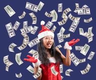 Dollar bills are falling around Mrs. Santa Claus. Cheerful Mrs. Claus looks at the camera with her hands showing flying money. Dollar bills are falling around stock photos