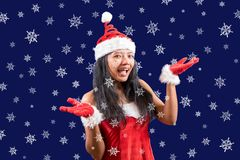 Cheerful Mrs. Claus shows snowflakes. Cheerful Mrs. Claus looks to the camera with her hands shows snowflakes. Hexagonal snowflakes fall around Mrs Claus royalty free stock photos