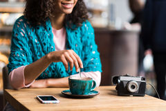 Cheerful mulatto girl drinking coffee in cafe stock photo
