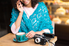 Cheerful mulatto girl talking on phone in cafe Stock Photography