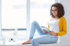 Cheerful mulatto woman holding tablet Royalty Free Stock Images