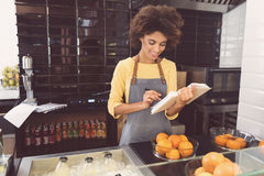 Cheerful mulatto woman is laboring in vegetarian shop stock images