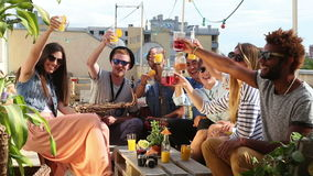 Cheerful multi-ethnic friends laughing and toasting with cocktails at rooftop. Cheerful multi-ethnic friends looking at camera, laughing and toasting with stock video footage