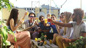 Cheerful multi-ethnic friends laughing and toasting with cocktails at rooftop. Cheerful multi-ethnic friends looking at camera, laughing and toasting with stock video