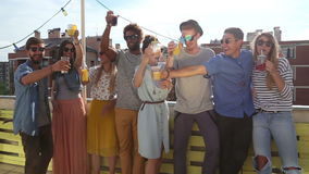Cheerful multi-ethnic friends standing at rooftop and toasting towards camera. Group of cheerful multi-ethnic friends standing at rooftop and toasting towards stock footage