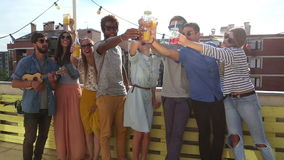 Cheerful multi-ethnic friends standing at rooftop and toasting towards camera. Group of cheerful multi-ethnic friends standing at rooftop and toasting towards stock video
