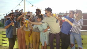 Cheerful multi-ethnic friends standing at rooftop and toasting towards camera. Group of cheerful multi-ethnic friends standing at rooftop and toasting towards stock video footage
