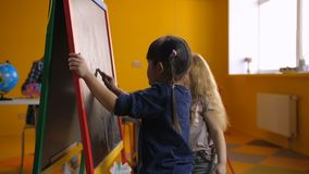 Cheerful multi ethnic girls drawing on chalkboard. Positive multicultural preschool girls drawing with chalks at blackboard in kindergarten while teacher with stock video