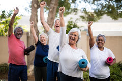Cheerful multi-ethnic seniors with exercise mats at park. Cheerful multi-ethnic seniors with arms raised carrying exercise mats at park Royalty Free Stock Image