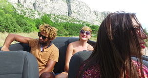 Cheerful multi ethnic students enjoying vacation driving in red convertible stock video footage