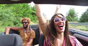 Cheerful multi ethnic students enjoying vacation driving in red convertible stock video