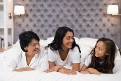 Cheerful multi-generation family lying on bed. At home Stock Photography