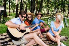Cheerful multicultural friends with beer and guitar resting. In summer park royalty free stock photos