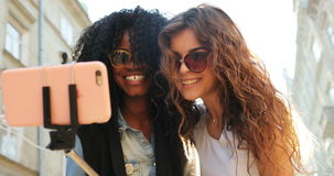 The cheerful multicultural girls are taking selfies. They are smiling and sending air kisses. The outdoor location. stock footage