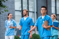 Cheerful multicultural medical students walking. Near medical university stock image