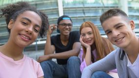Cheerful multiethnic teen friends smiling at camera, leisure time together