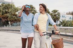 Laughing trendy diverse couple with bicycle royalty free stock photography