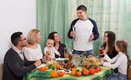 Cheerful multigenerational family sitting at holiday table Royalty Free Stock Photo