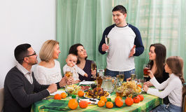 Cheerful multigenerational family sitting at holiday table Stock Photos