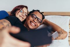 Multiracial couple taking selfie in bed. Cheerful multiracial couple lying together in bed and taking selfie. Smiling men and women making selfie with mobile Royalty Free Stock Images