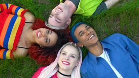 Cheerful multiracial female and male hipsters lying grass and laughing, friends stock footage