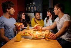 Cheerful multiracial friends having fun eating  in pizzeria. Stock Photo