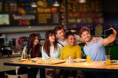 Cheerful multiracial friends having fun  eating in pizzeria. Stock Photos