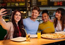 Cheerful multiracial friends taking selfie in  pizzeria. Royalty Free Stock Photos