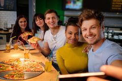 Cheerful multiracial friends taking selfie in  pizzeria. Stock Photos