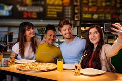 Cheerful multiracial friends taking selfie in  pizzeria. Royalty Free Stock Image