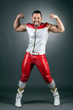 Cheerful muscular dancer shows biceps at camera Stock Photography