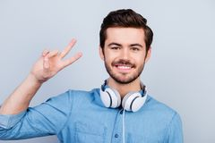 Cheerful music fan is showing peace sign. He is wearing stylish. Jeans shirt, behind him is light blue background stock photos
