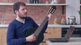 Cheerful musician guy practicing play guitar uses laptop computer with online video tutorial and delight music. At home stock footage