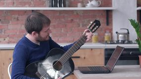 Cheerful Musician men learning play guitar uses laptop computer with online video teaching and enjoy music. At home stock footage