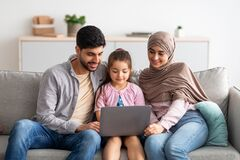 Cheerful muslim family having fun with laptop, surfing internet, playing games or having video chat, sitting on sofa