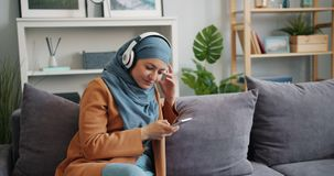 Cheerful Muslim girl in hijab using smartphone listening to music in apartment. Cheerful Muslim girl in hijab is using smartphone and listening to music in stock footage
