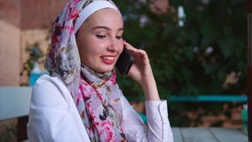 Cheerful Muslim woman having a phone talk stock video footage