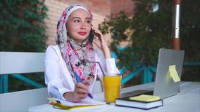 Cheerful Muslim woman having a phone talk. Slow motion shot of young Muslim woman in outdoor cafe. She laughing and smiling when talking on mobile stock video