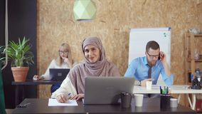 Cheerful muslim woman is smiling broadly in office room looking at camera