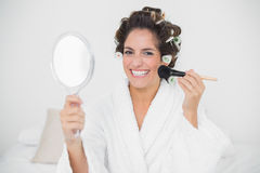 Cheerful natural brunette using brush and mirror Stock Image