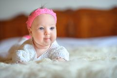 Cheerful newborn baby with a beautiful pink crown on the head, lies on white fluffy fur royalty free stock photo