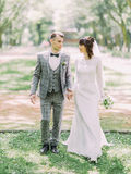 Cheerful newlywed couple is holding hands and walking in the park. Royalty Free Stock Images