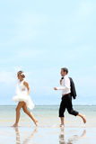 Cheerful newlywed couple playfully at the beach Royalty Free Stock Photography
