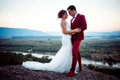Cheerful newlywed couple is tenderly hugging on the mountains at the background of the landscape during the sunset. royalty free stock photo