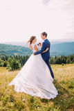 Cheerful newlyweds drinking wine outdoors, celebrating their marriage. Nature background Stock Image